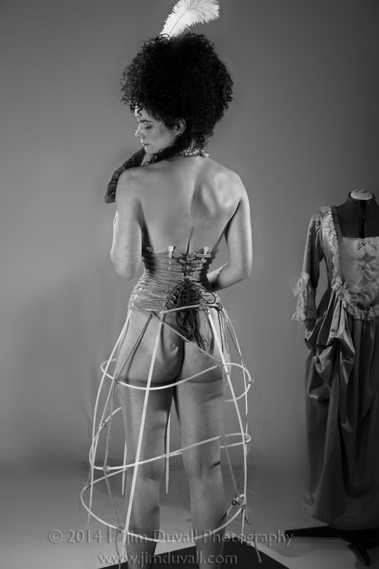 nude woman in a rope corset in a hoop skirt frame