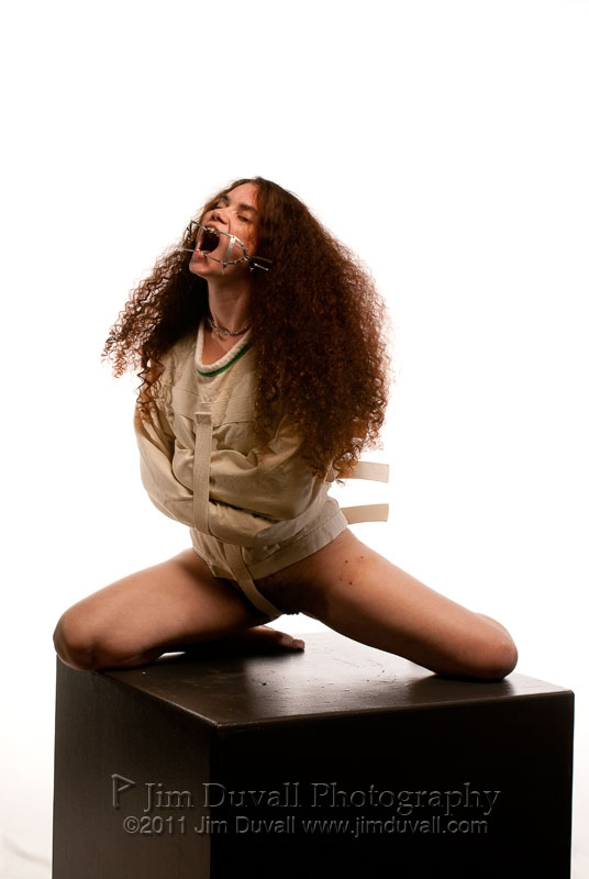 Woman in straight jacket and gag on pedestal