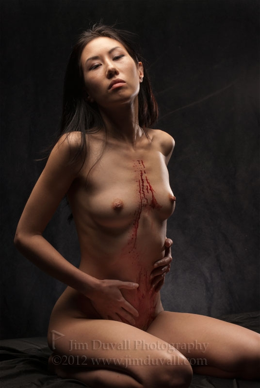 woman with blood on her torso from the removal of numerous body piercings