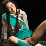 woman in a girl scout uniform exposing her vulva with needls in it in a pattern like teeth.
