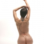 woman on her knees with needles on her back in an artistic pattern